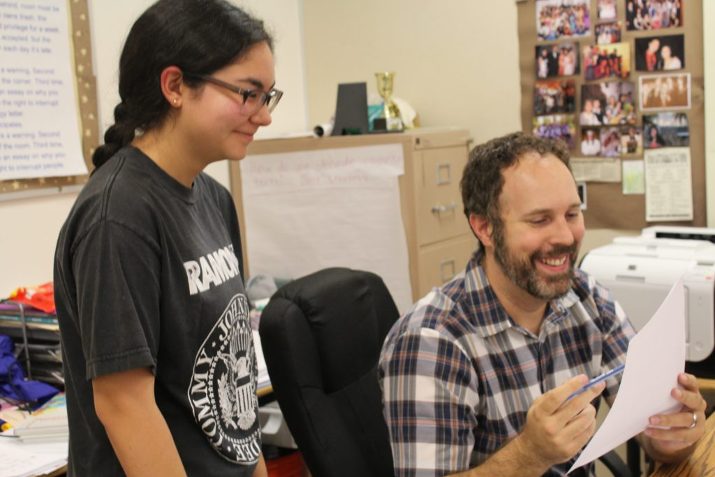: Journalism Adviser Timothy Ritenour helping out a journalism student with her article